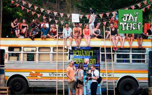 people sitting on top of bus at jai thep festival in thailand